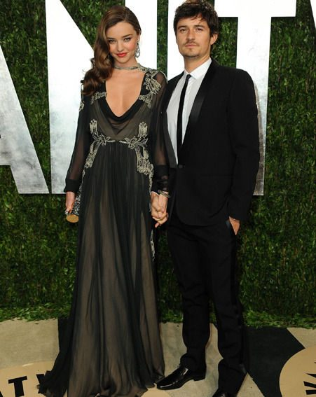 Miranda Kerr and hubby Orlando Bloom hold hands as they pose on the red carpet